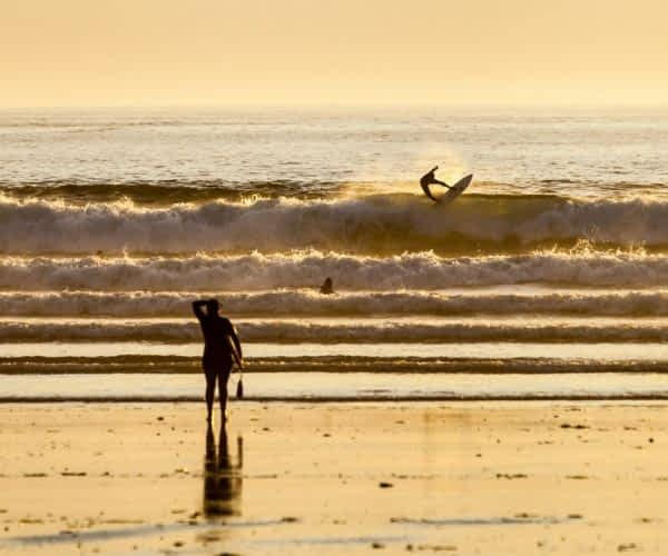 Silhouette of spectators watching surfer at sunset on Long Beach, Tofino BC